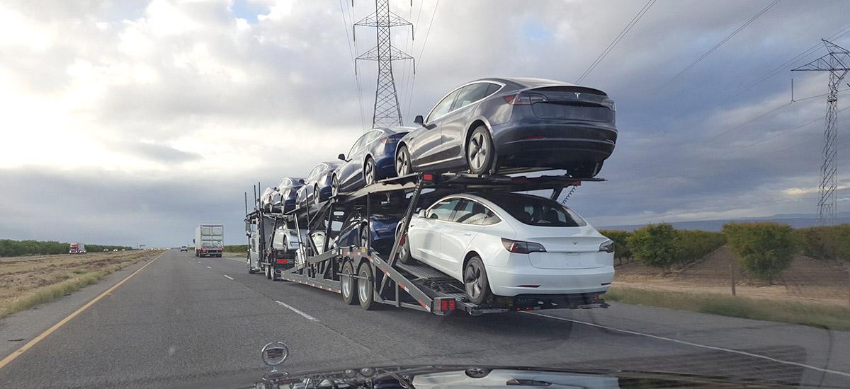 Tesla Model 3 on highway for deliveries