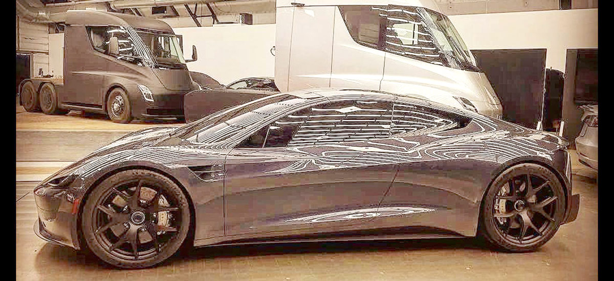 Tesla Roadster leaked photo from inside Tesla factory. Tesla Semi trucks also in background.