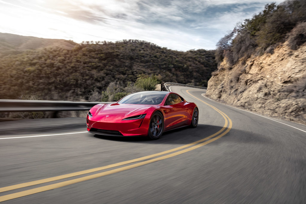 Tesla Roadster in red color - racing on the mountains