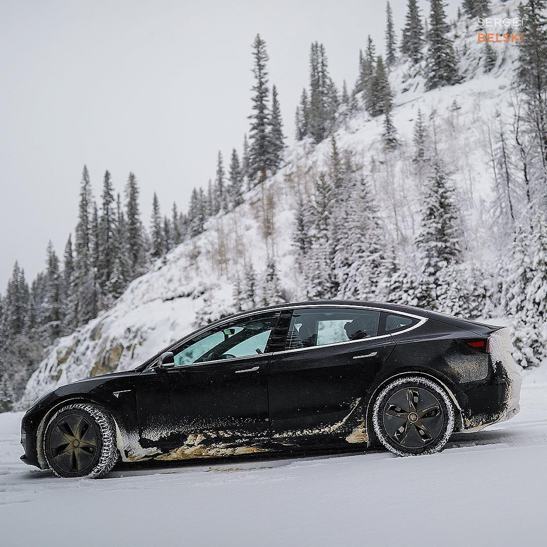Black Tesla Model 3 In Snow Side View Driving