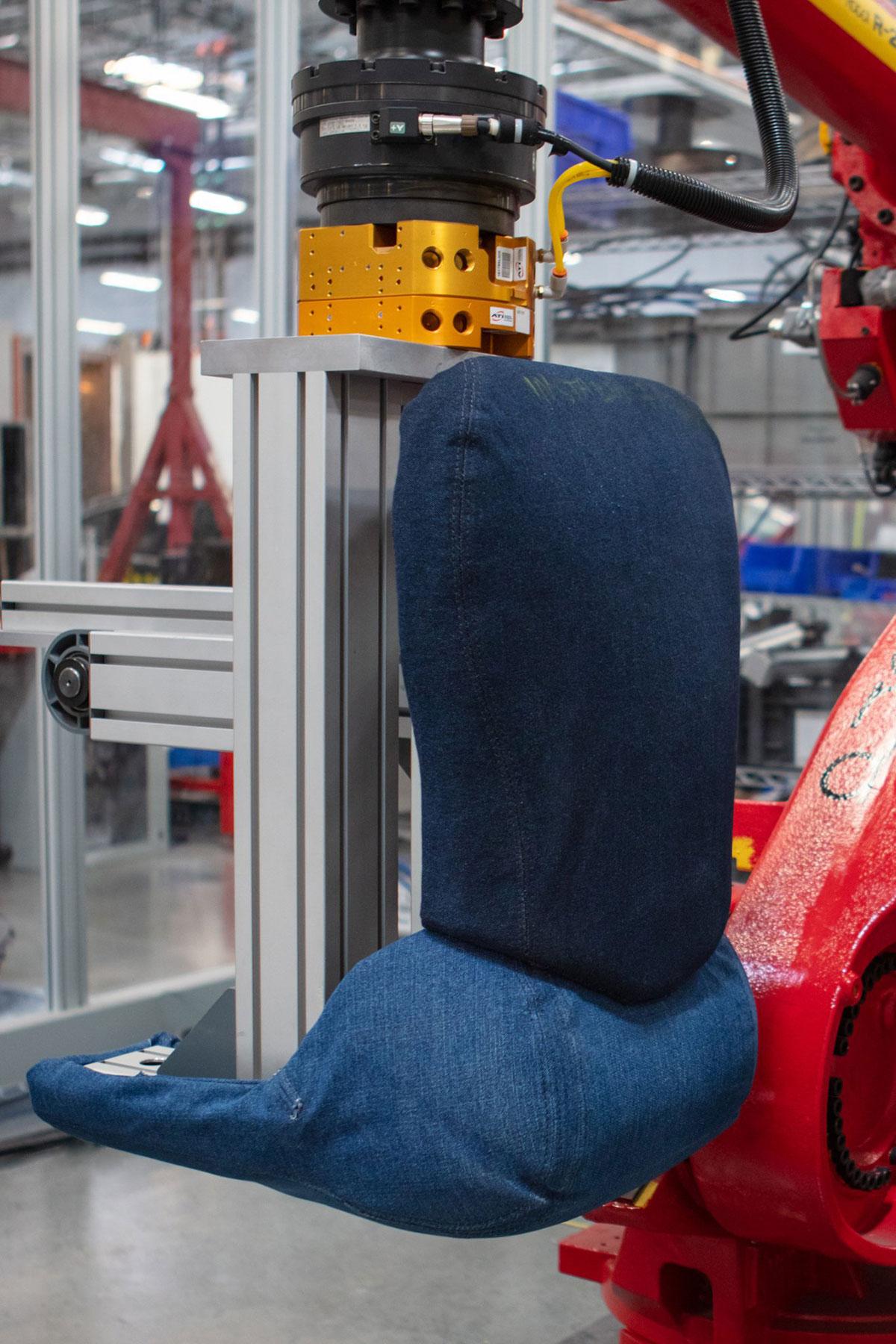 Tesla Model 3 seat tester model wearing blue jeans for stain resistance testing.