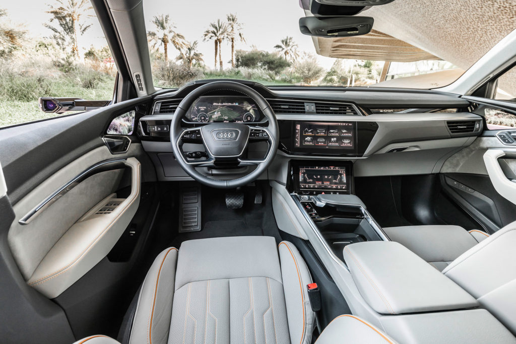 Audi e-tron interior cabin shot. Multi-tier dashboard with dual center touchscreens.