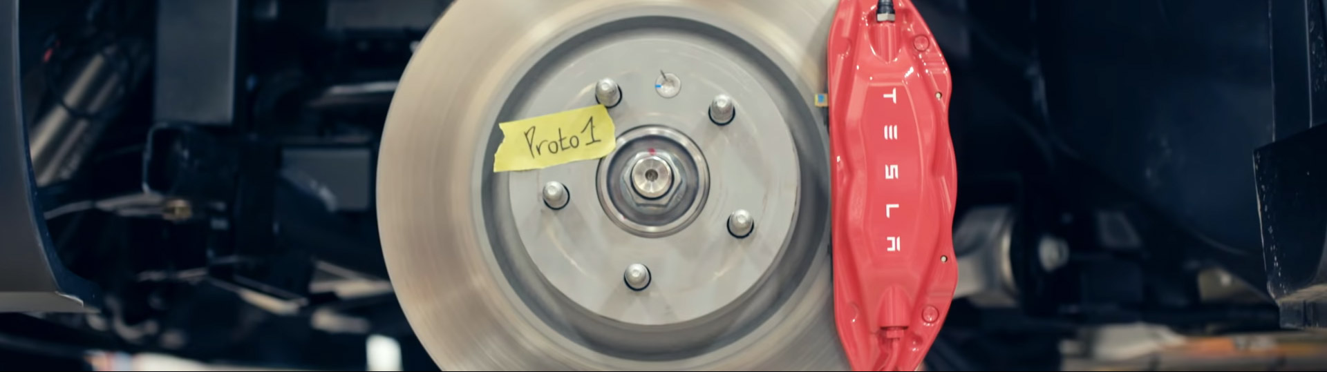 Wheel with 'Proto 1' tag with red Tesla brake calipers