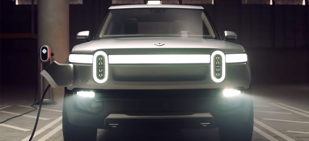 Rivian R1T Electric Pickup Truck - Front view with charge port plugged-in