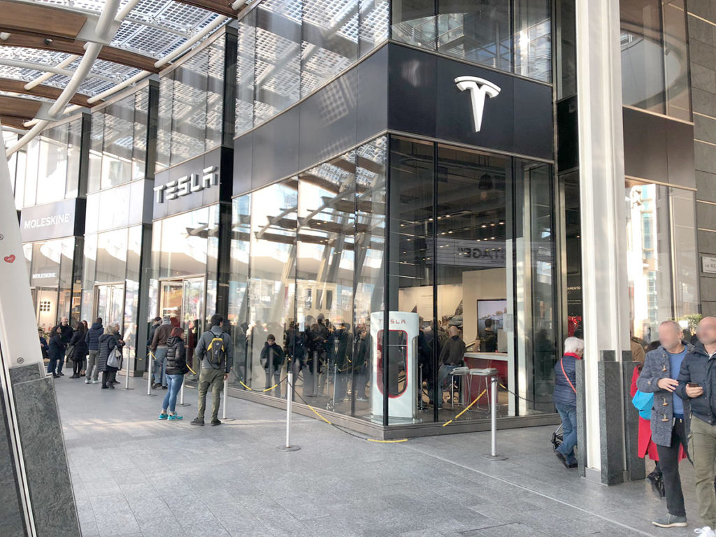 Tesla Model 3 Europe display at the Tesla Store in Milan, Italy. People waiting in line for their turn to experience the Model 3 electric car.