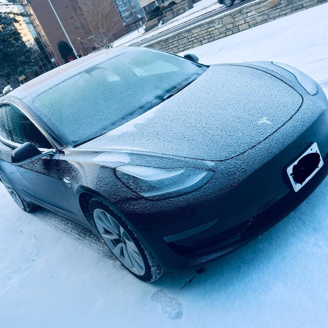 Black Tesla Model 3 in Snow - small snowflakes covering the bonnet and roof
