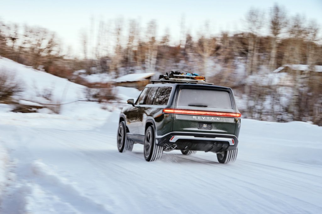 Rivian R1S electric SUV accelerating in the snow - rear view