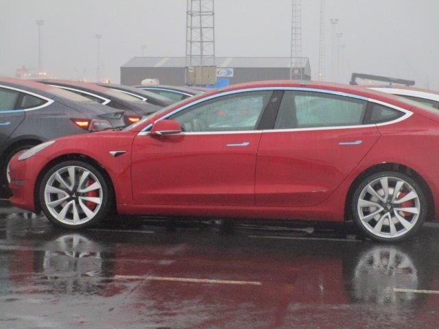 Tesla Model 3 vehicle fleet at the Port of Zeebrugge, Belgium - red Model 3 side view profile