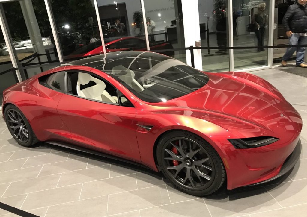 Next-gen Telsa Roadster in red color at a Tesla facility - side profile view