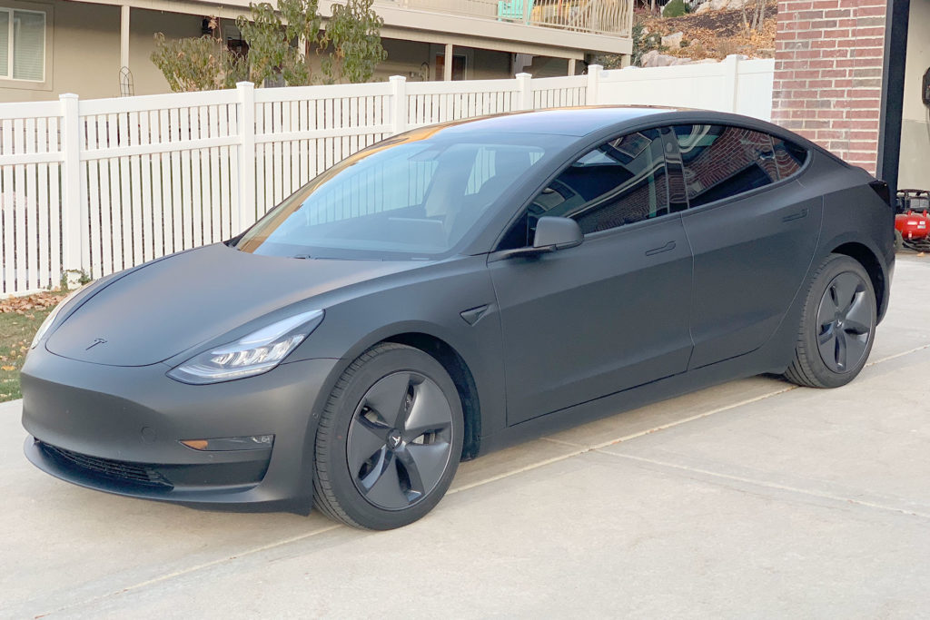 Tesla Model 3 wrapped in matte black, sitting in the driveway