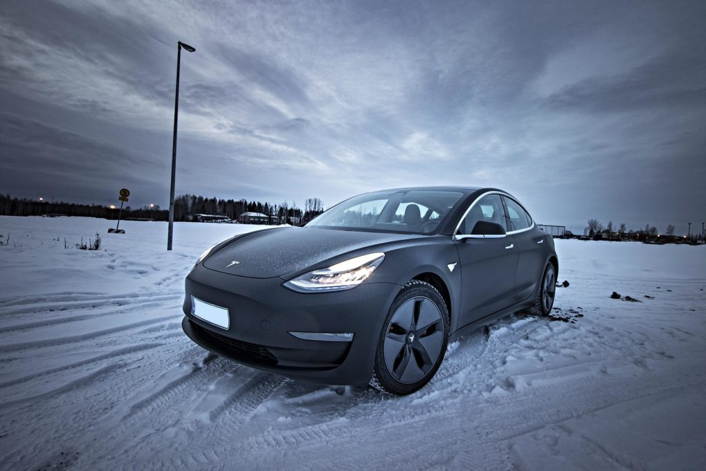 Matte Black Tesla Model 3 in Hämeenlinna, Finland, standing in snow at the golden hour.