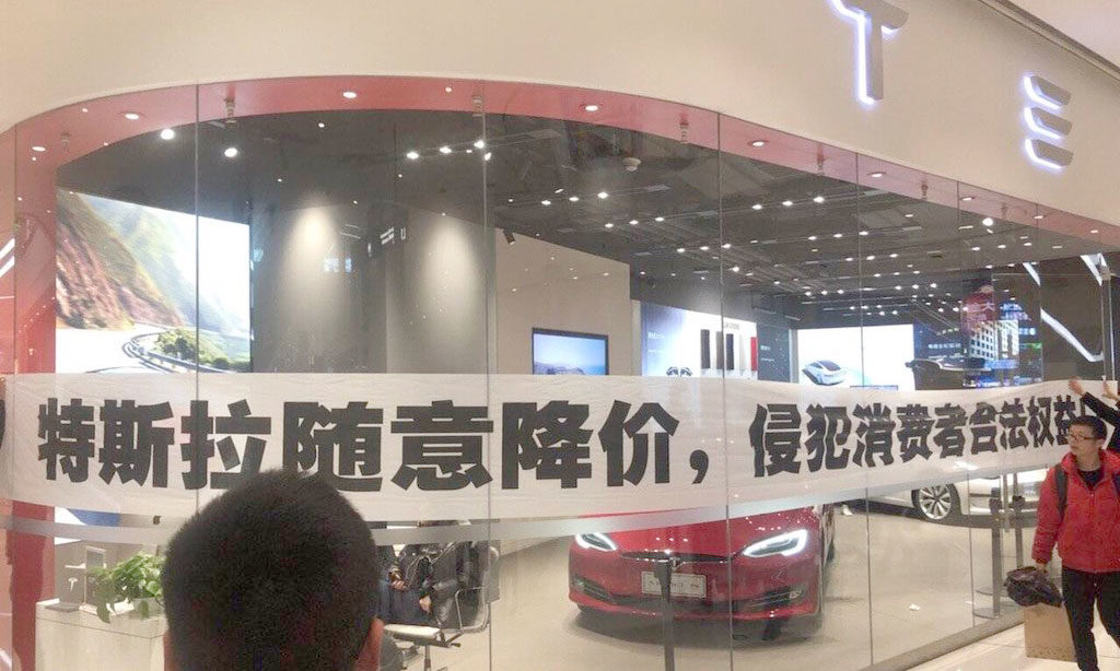People affixed a banner on Tesla China Store which says, 'don't buy these cars, they will be cheaper tomorrow'