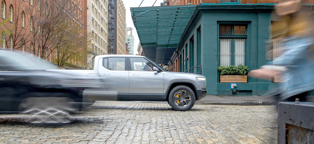 Rivian R1T Pickup Truck followed by R1S SUV at high speeds.