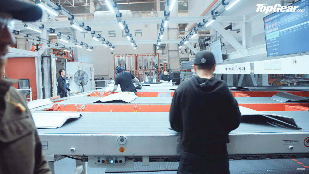 Humans working in Tesla Fremont Factory - checking the door panels and sanding off the edges to be stacked and installed later.