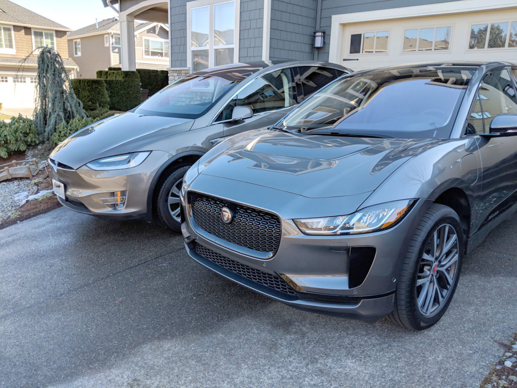 Tesla Model X and Jaguar I-Pace parked side-by-side, photo shows visual size comparison from the front -right angle.