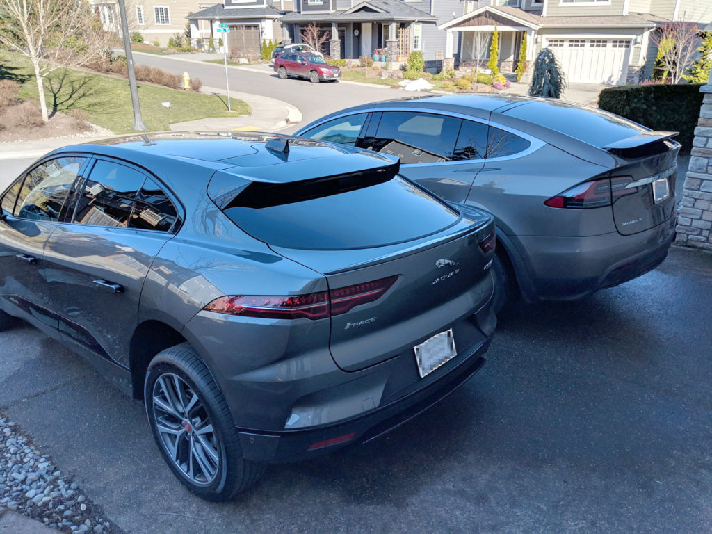 Tesla Model X and Jaguar I-Pace parked side-by-side, photo shows visual size comparison from the rear-left angle.