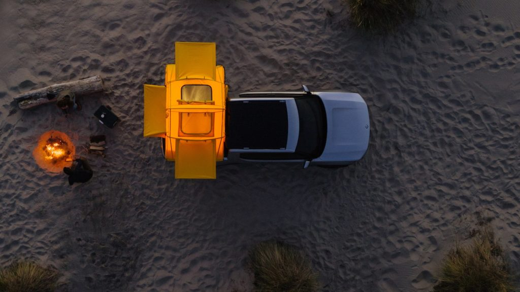 Rivian R1T Pickup Truck with camp on the back, light inside the camp at night time.