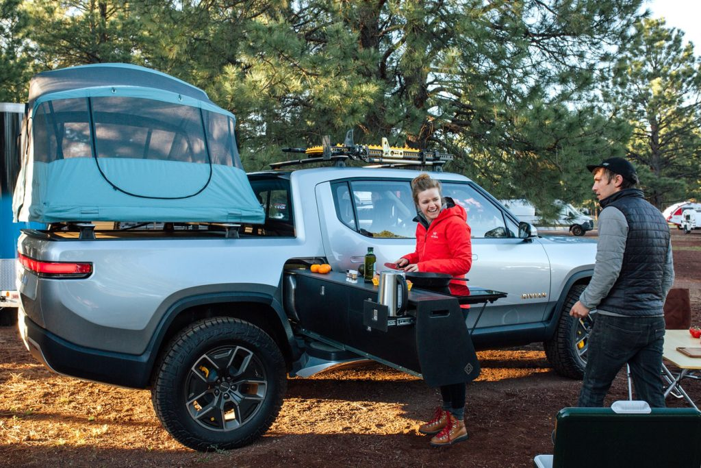 Rivian R1T electric pickup truck with small camp and mobile kitchen setup.