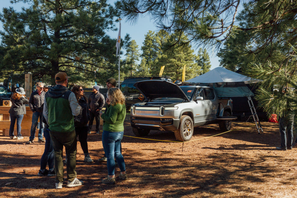 Rivian R1T pickup truck with medium sized camp on trailer bed.