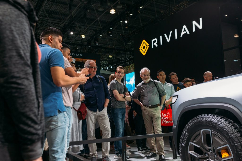 Audience at the New York Auto Show admiring the looks of the Rivian R1T Pickup Truck.
