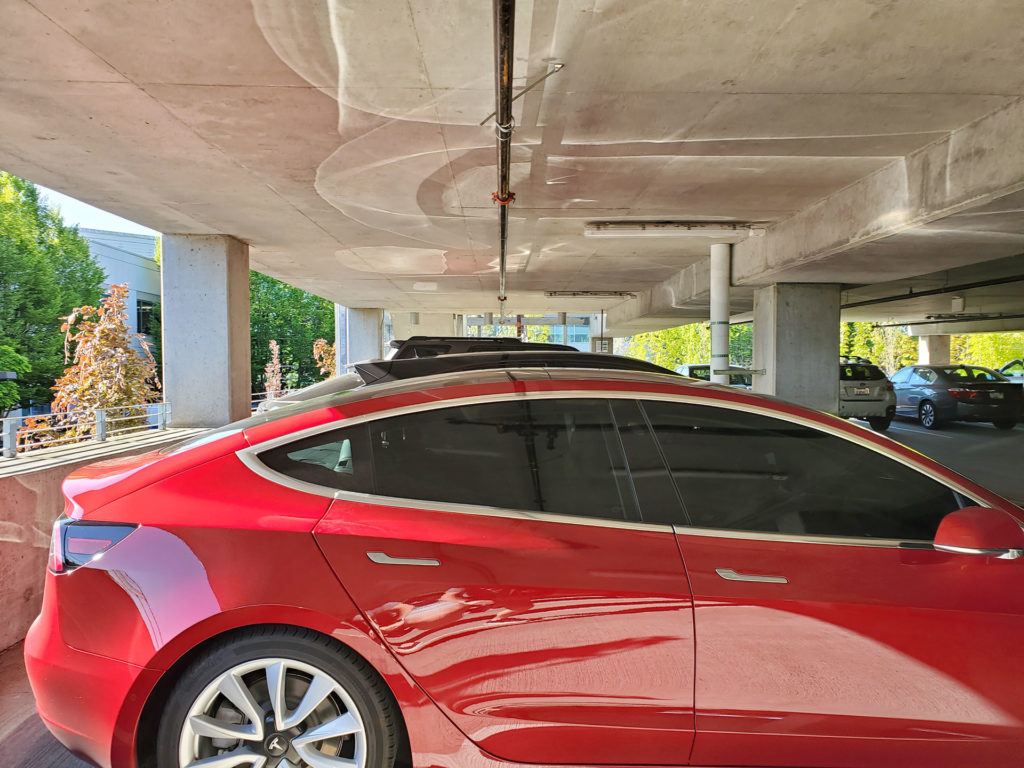 Tesla Model 3 and Jaguar I-Pace standing side-by-side in a parking lot - rear angle comparing height.