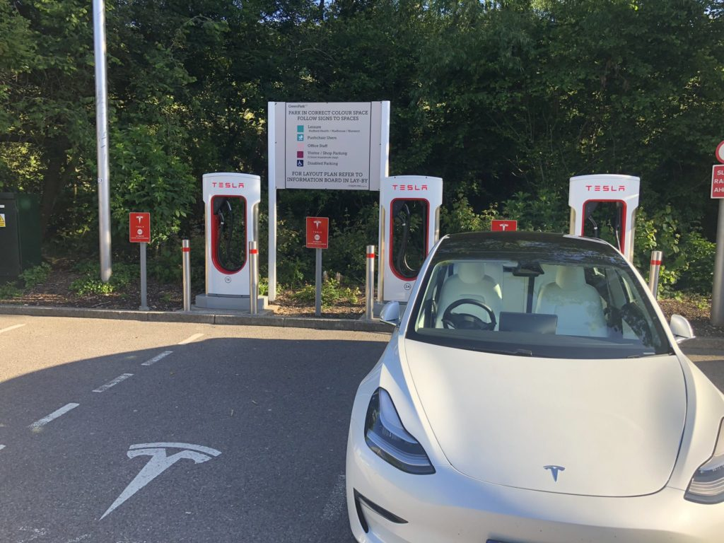 White RHD Tesla Model 3 Supercharging at the Green Park Reading Supercharger in the UK.