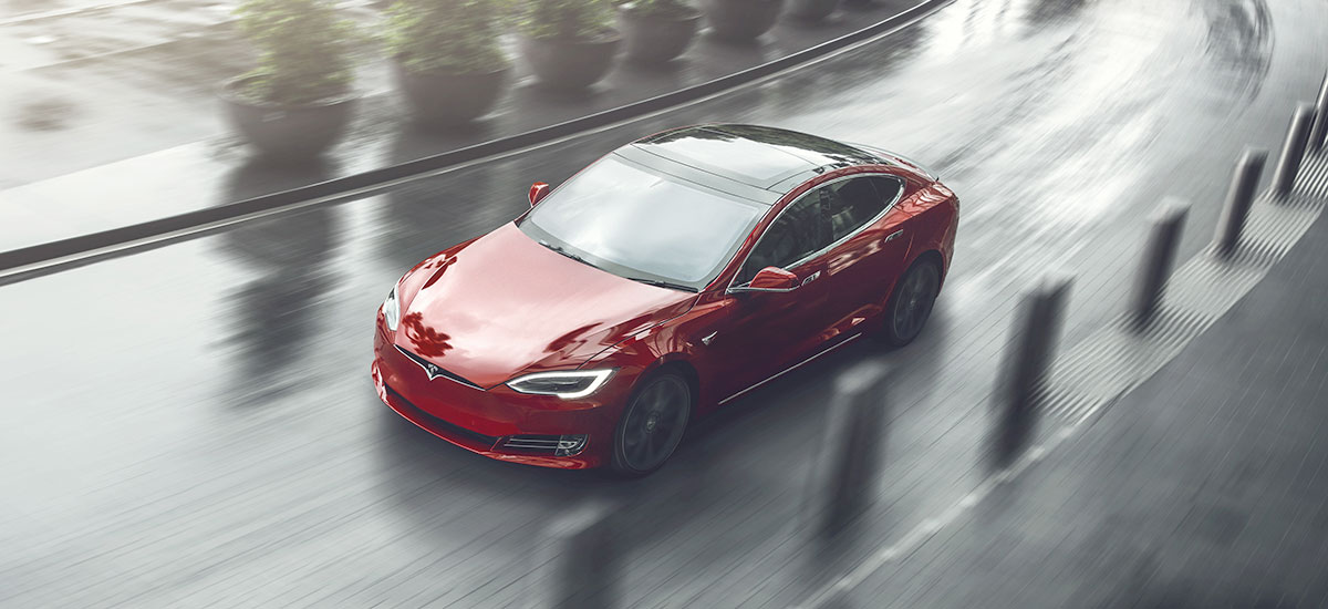 Tesla Model S in red color, roaming the city.