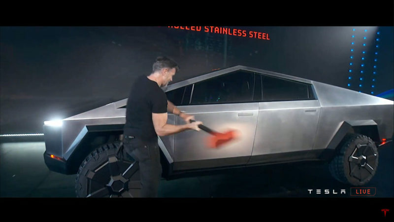 Tesla Chief Designer Franz Von Holzhausen hitting the Cybertruck with a sledgehammer for toughness demonstration.