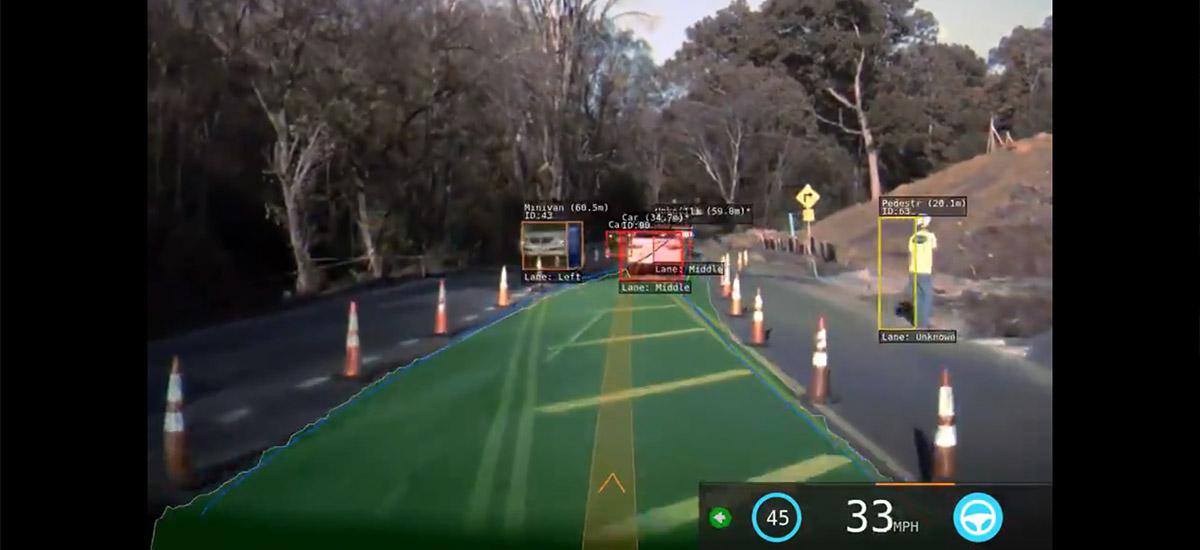 Tesla Autopilot vision in a construction zone with traffic cones on both sides.