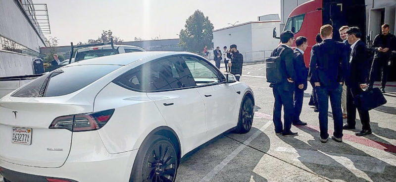 Tesla Model Y Performance with black wind turbine wheels spotted at the Tesla Fremont car factory, red Tesla Semi in the background.