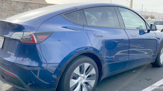 Tesla Model Y Prototype in Blue Color at a Supercharger station.