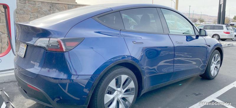 Tesla Model Y Prototype in Blue Color at a Supercharger station.