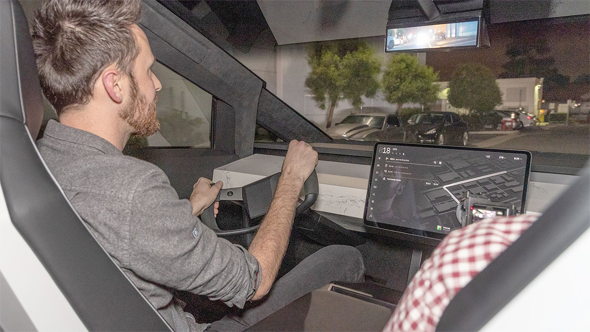 Tesla Cybertruck interior photo (steering wheel, center touchscreen and rearview screen visible in the shot).