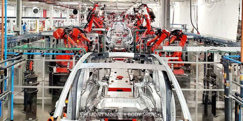 Model Y compact electric SUV body shop at the Tesla Fremont car factory. Robots working on the Model Y assembly line.