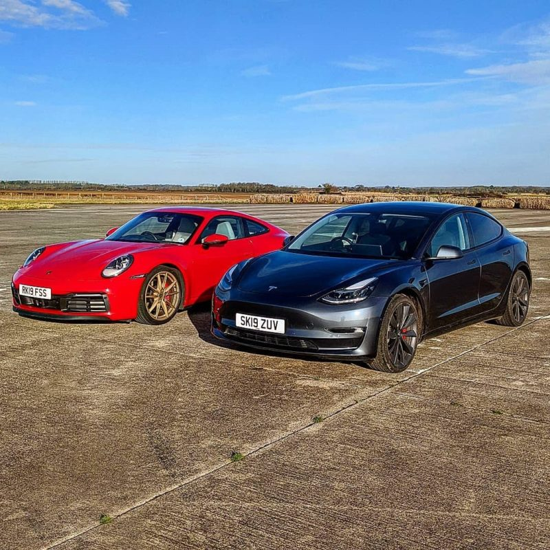Tesla Model 3 Performance and Porsche 911 Carrera side-by-side on the drag strip, just before the race (front view).