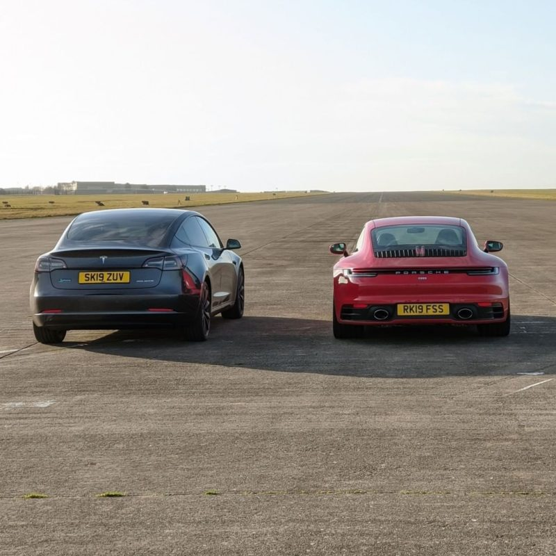 Tesla Model 3 Performance and Porsche 911 Carrera side-by-side on the drag strip, just before the race (rear view).