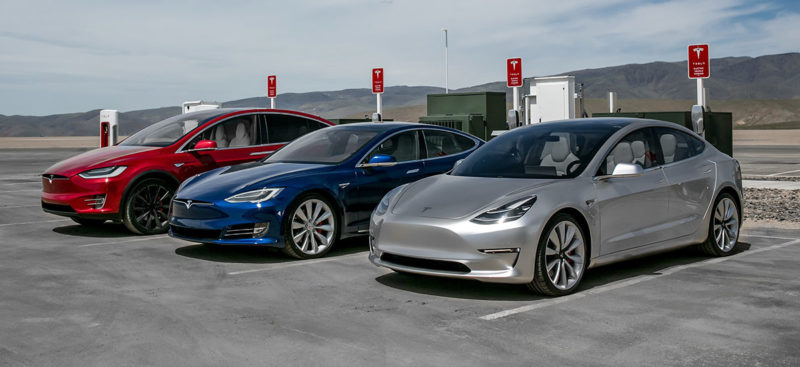 Tesla Model 3, S, and X at a Supercharger station.
