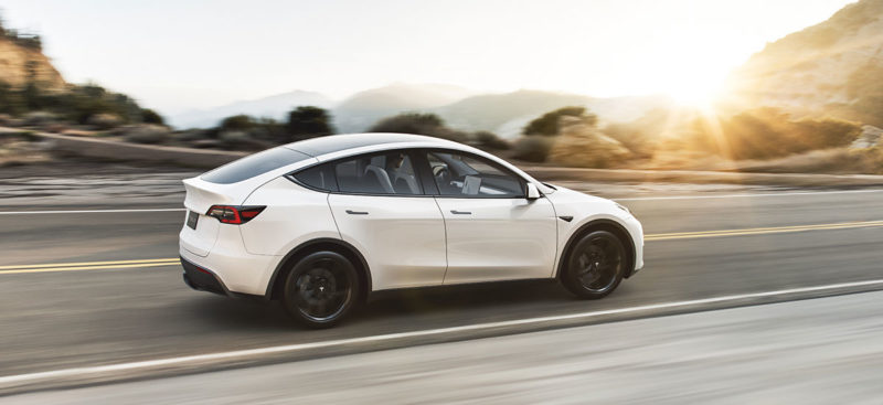 White Tesla Model Y cruising on highway at sunset. Production started in Jan 2020, deliveries expected Mar 2020 as per Q4' 2019 Earnings Call.