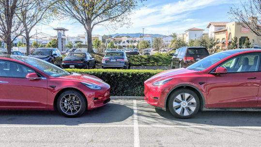 Tesla Model 3 and Tesla Model Y standing opposite each other in a parking lot, giving us an idea of the size comparison of both vehicles.