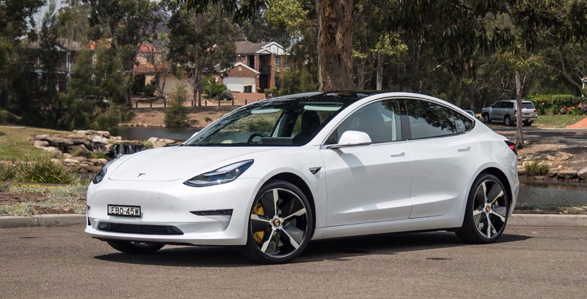 White Tesla Model 3 compact electric sedan with Porsche Taycan wheels.