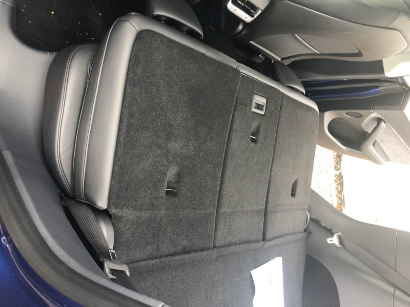 Tesla Model Y trunk with seats down - side view from the rear door.