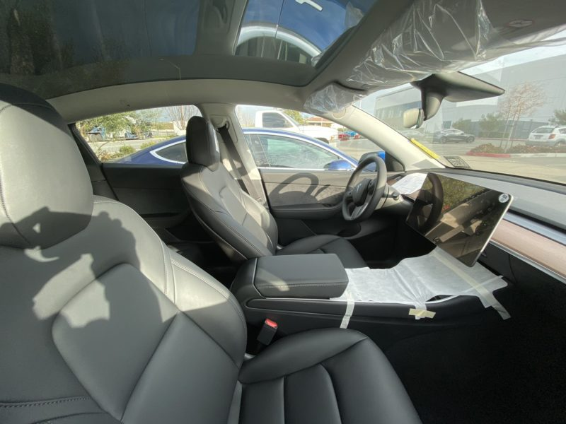 Tesla Model Y Interior - 1st row seats, center touchscreen, steering wheel, windshield.