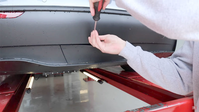 Finding the Tesla Model Y tow hitch under the rear diffuser panel.